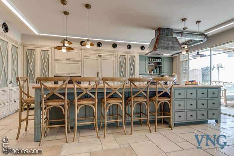 מטבח כפרי רחב ומרשים עם כסאות בר והרבה פינות אחסון
